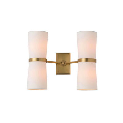 Modern double wall sconce with cylindrical linen shades and antique brass arms and backplate.