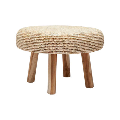 The Kailua Stool is a small stool with a round, raffia pillow top and teak legs.