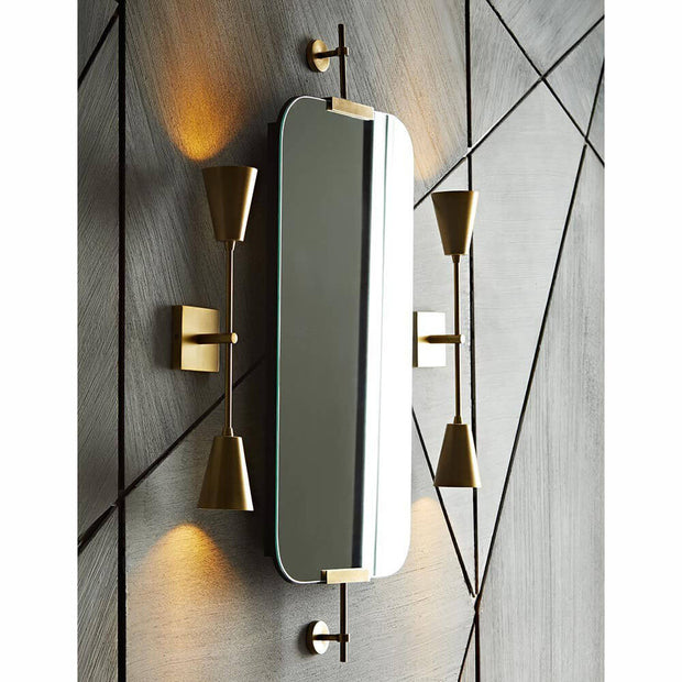 The modern mirror with antique brass brackets hanging vertically in a contemporary bathroom.