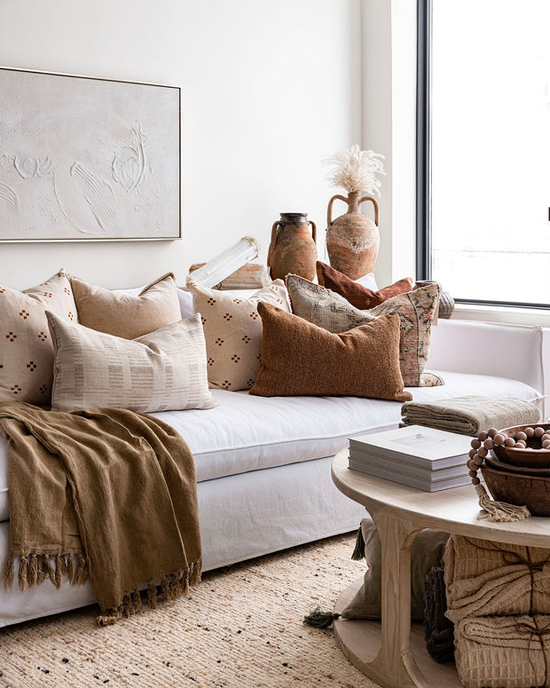 White textured artpiece with neutral pillows and white sofa.