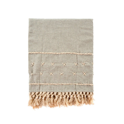 Marie Cross Stitch Throw features delicate cross stitching an tassels in a warm beige against the stone grey linen.