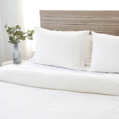 The Marietta Blanket Collection in cream is made from stonewashed cotton and has a small waffle weave texture.
