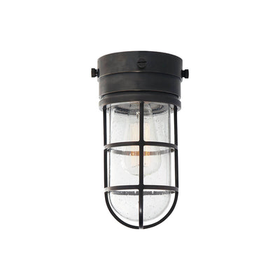 The Marine Flush Mount is an industrial looking caged light with a bronze base and a seeded glass shade.