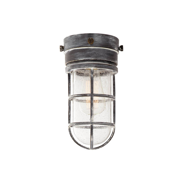 The Marine Flush Mount is an industrial looking caged light with a weathered zinc base and a seeded glass shade.