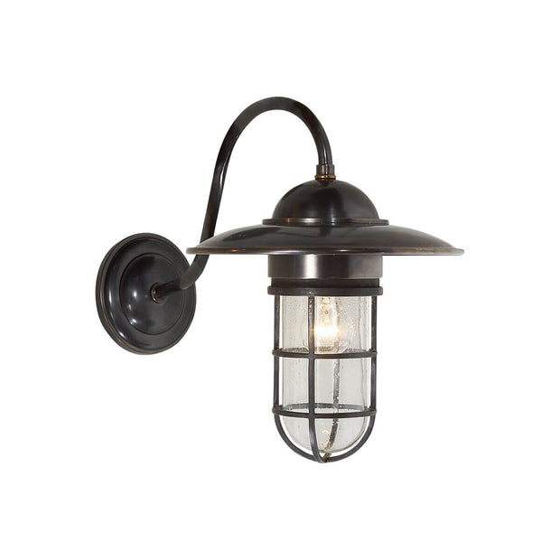 The Marine Wall Sconce is inspired by traditional marine lights and has a bronze backplate, hooked arm and lamp shade and a seeded glass shade.