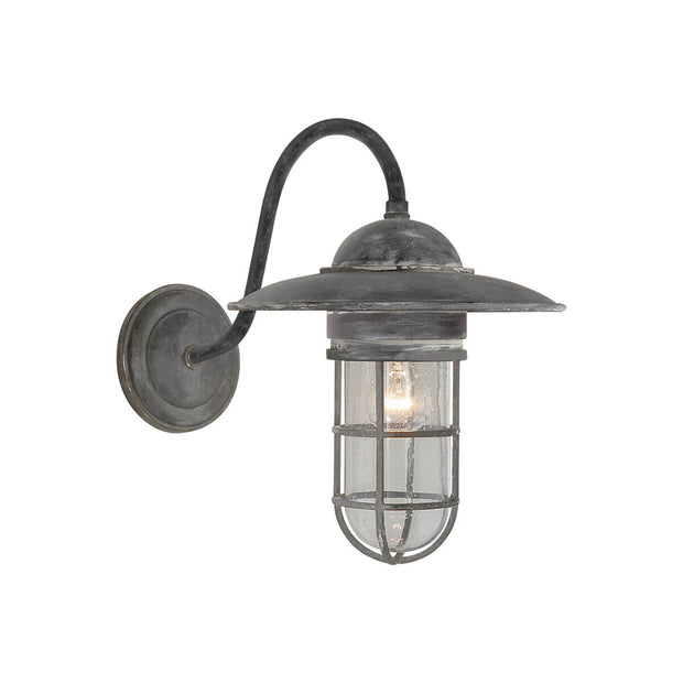 The Marine Wall Sconce is inspired by traditional marine lights and has a weathered zinc backplate, hooked arm and lamp shade and a seeded glass shade.