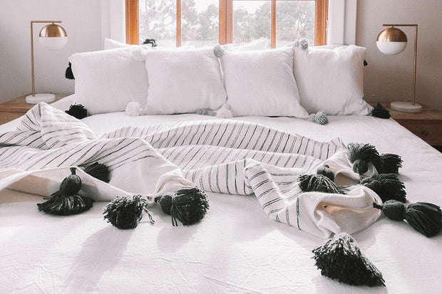 Charcoal and white throw blanket with pom pom trim on a white bed.