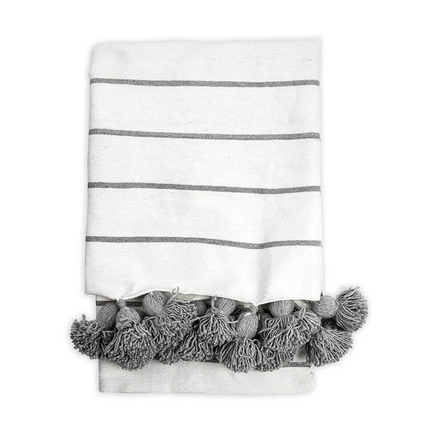 White and light grey striped cotton throw blanket with grey tassel trim.