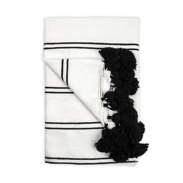 The Casablanca Throw - Black is a white with black striped, 100% cotton woven blanket with pom-pom trim.