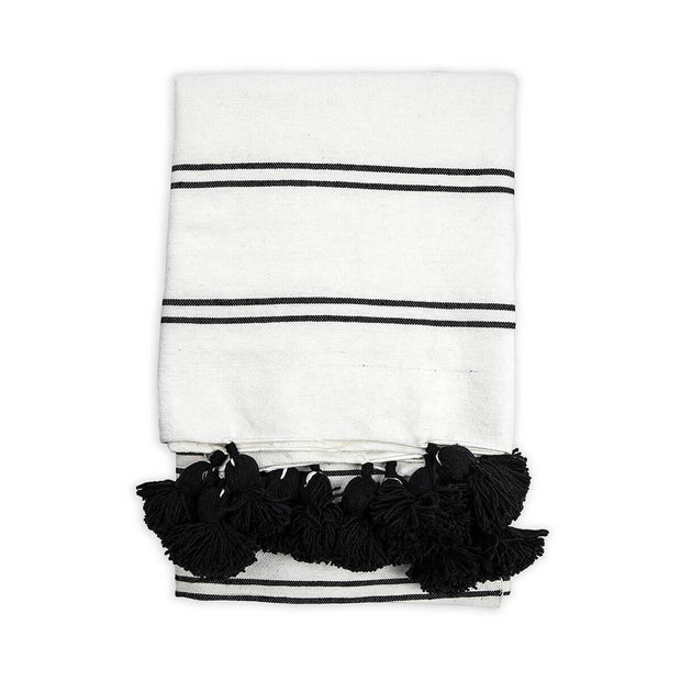 Black and white striped thrown blanket with black pom-pom trim.