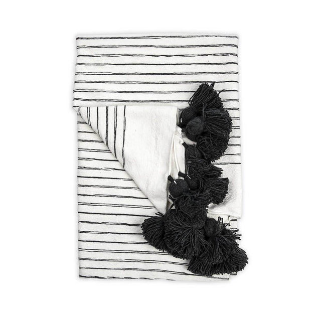 The Casablanca Throw - Black is a white with charcoal striped, 100% cotton woven blanket with pom-pom trim.