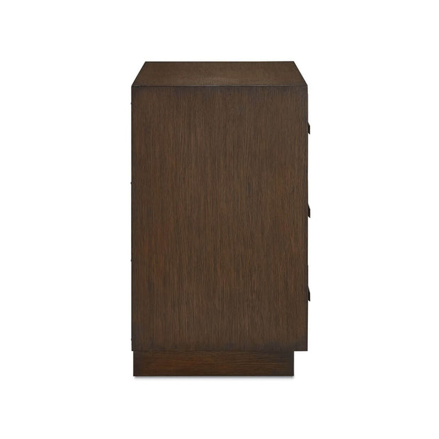 Side view of a dark brown chest with 3 drawers with carved geometric patterns on the front.