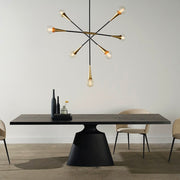 Modern dining table with a stand-alone architectural base and a floating top in a dark onyx tone. Dining table under modern chandelier.