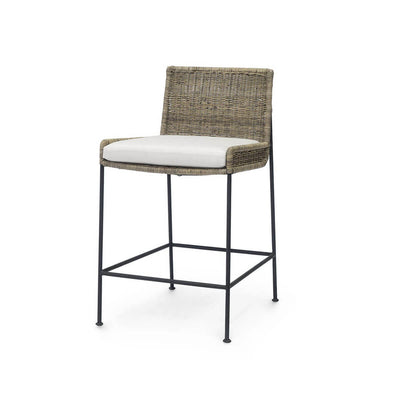 The Belle Fourche Counter Stool has a black metal frame, natural rattan seat and back, and upholstered, loose seat cushion.