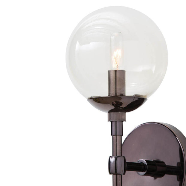 Clear glass globe lamp shade and brown nickel details on the Navala Wall Sconce.