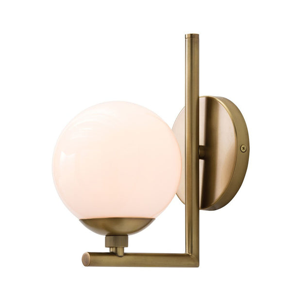 The Livno Wall Sconce in an antique brass finish with a frosted glass lampshade and metal arm detail.