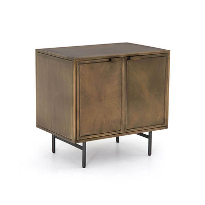 The Reseda Nightstand is made of aged brass and has an etched sunburst pattern on the front and H-stretcher legs.