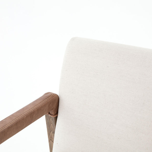 Closeup of the white backrest cushion and leather arm details on the comfortable dining chair.
