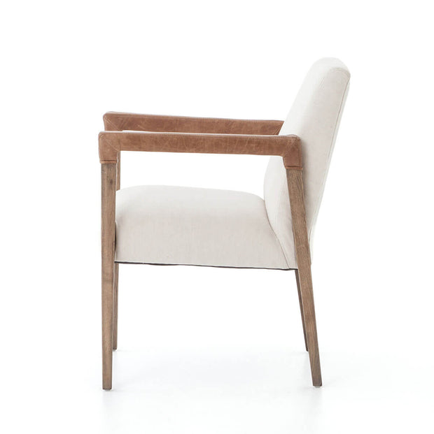 Side view of the elegant dining arm chair with white linen cushions and tapered oak legs.