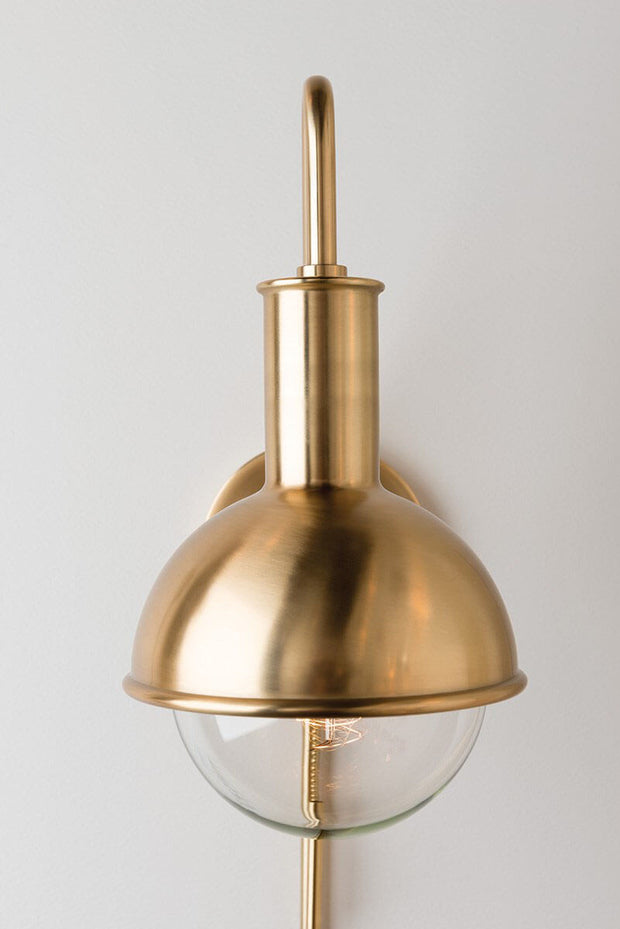 Aged brass modern looking wall sconce with a round glass bulb.