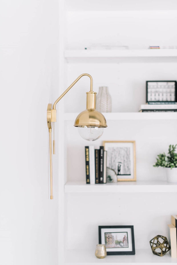 Aged brass wall sconce with adjustable arm in a white living room.
