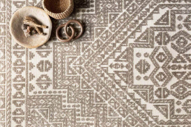Neutral, ornate rug with a geometric pattern and low pile.