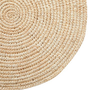 Closeup of a woven, round piece of natural wall art.