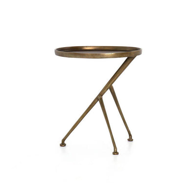 The Rostock Accent Table has a oval tabletop, tripod legs and is made of cast aluminum in a raw brass finish.