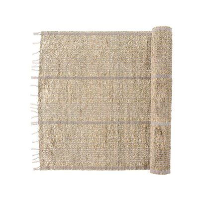 The Seagrass Table Runner - Grey is a woven table runner made from seagrass and grey cotton with a fringed edge.