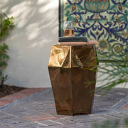 The crackled gold ceramic stool has a gemstone inspired shape and is water-resistant.