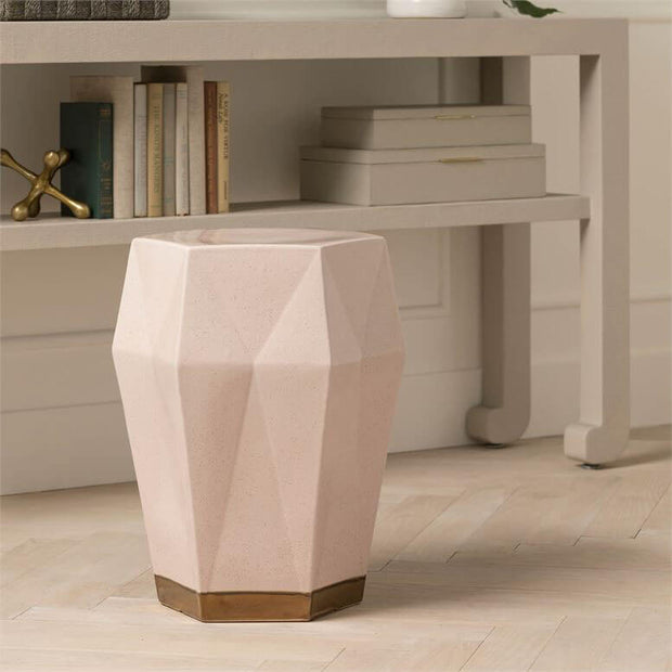 Modern geometric shape stool with a pink finish with gold details in a living room.
