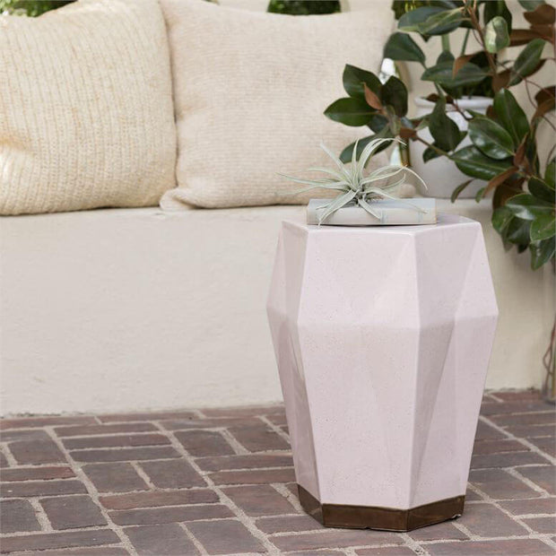 A light pink ceramic stool on a cozy outdoor patio.