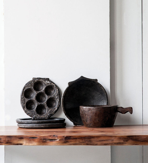 Hand-carved stone plates on a wooden shelf.