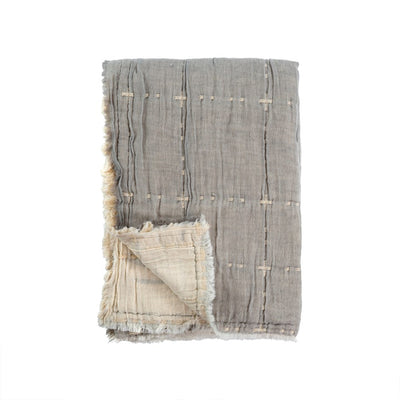 The Suez Quilted Throw - Light Grey is a double-faced throw with a cool frayed edge and a soft gauzy weave.