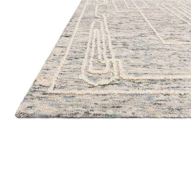 Hand tufted rug with abstract geometric designs.