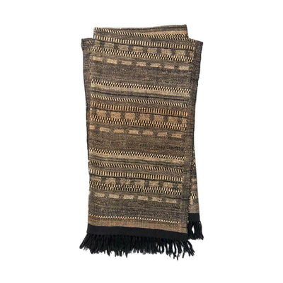 The Tejada Throw - Black / Beige is a luxurious, wool and silk blend throw blanket with a black and beige ancient tribal pattern.