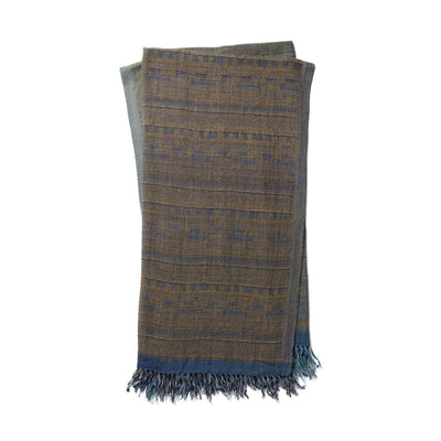 The Tejada Throw - Blue / Grey is a luxurious, wool and silk blend throw blanket with a blue and grey, ancient tribal pattern.