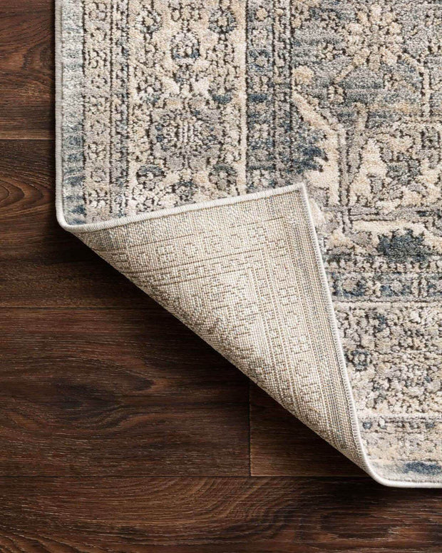 Vintage inspired rug with a light brown and blue traditional pattern and low pile.