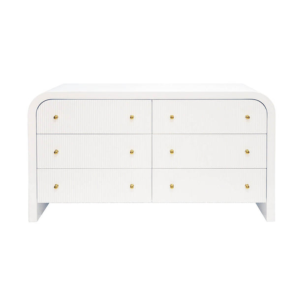 The Pavia Dresser is a waterfall dresser with a white lacquer finish, fluted front and gold hardware.