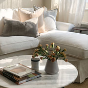 Romantic living room with white slipcovered sofa and velvet cushions.