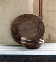 Teak wood bowls in various sizes on a shelf.