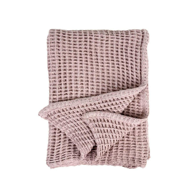 The Hobart Throw is a pink, waffle weave throw blanket.