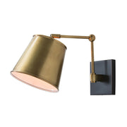 A mid-century modern wall sconce with antique brass details and an adjustable shade.