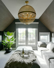 Lifestyle shot of the Mill Globe Lantern, a large gild pendant light with a globe shade and a chain hanger.
