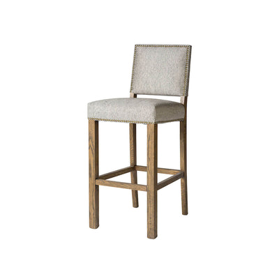 Classic counter stool with a light grey upholstered seat, solid birch wood legs in a weathered oak finish and stud details.