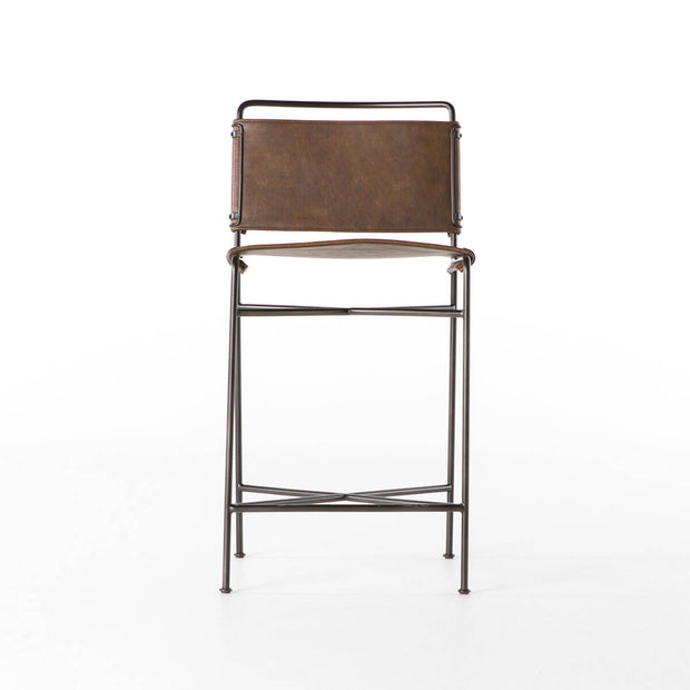 The Stowe Counter Stool has a simple steel tube frame and contoured distressed brown leather seat and backrest.