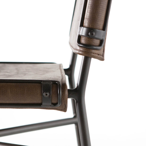 Metal details and distressed brown leather seat.