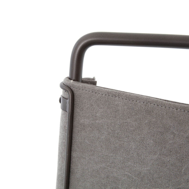 Closeup of the black metal tubing frame and stonewash grey cotton backrest with stitching details.