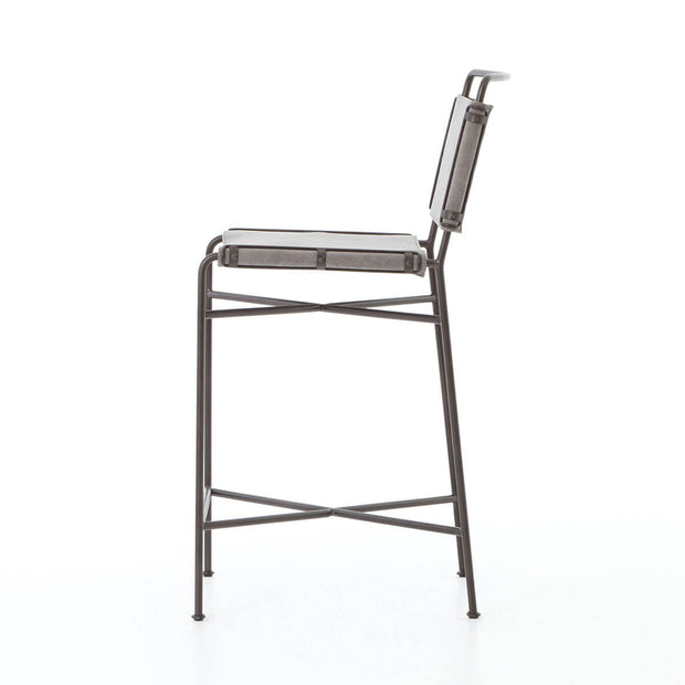 Sideview of a minimal counter stool with a simple metal frame and grey cotton seat.