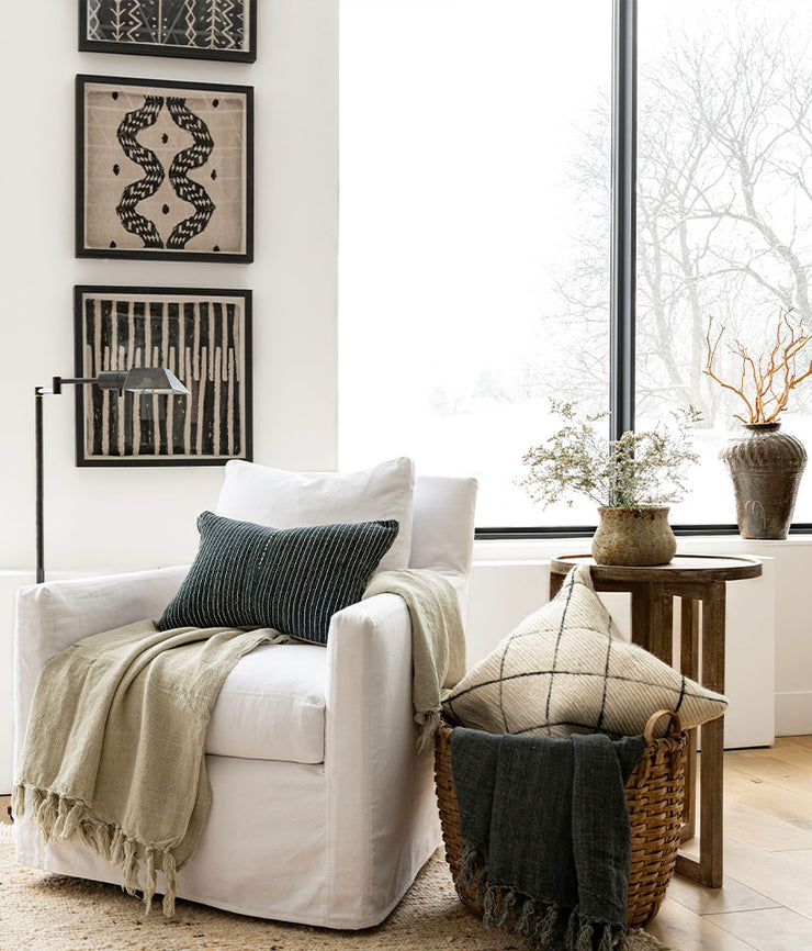 Woven tribal art showcased above white upholstered lounge chair with throw blankets and pillows, with a snowy winter scene outside.
